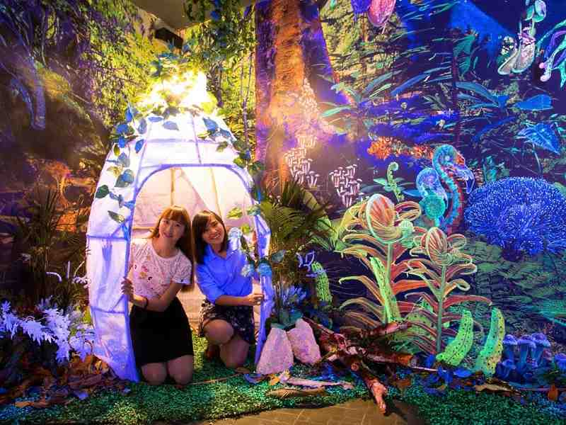 two girls posing at the glow in the dark area of the dark mansion penang