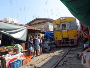 during this market tour of thailand you'll be able to see this maeklong railway market - a place where train runs through hawker areas